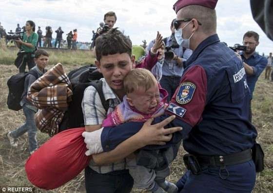 2C13F60500000578-3226888-A_Hungarian_policeman_attempts_to_stop_a_migrant_boy_carrying_a_-a-55_1441742675387