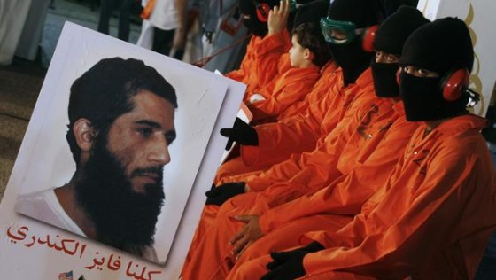 Protesters dressed in orange prison outfits and black masks attend a demonstration outside the US embassy in Kuwait City on May 2, 2012, calling for the release of Kuwaiti prisoners still behind the bars at the US detention camp in Guantanamo Bay. Fawzi al-Odah and Fayez al-Kandari (portrait) are the only two Kuwaitis still held at the US prison. AFP PHOTO / YASSER AL-ZAYYAT (Photo credit should read YASSER AL-ZAYYAT/AFP/GettyImages)